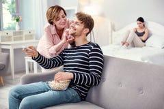 选择电视频道的快乐的成人人 免版税库存照片