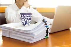 选择的焦点咖啡在堆的与事务的文书工作 免版税图库摄影