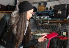 选择皮革钱包的美丽的少妇 免版税图库摄影