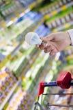 选择省能源的照明设备:在拿着或选择LED二极管电灯泡灯的男性或女性手上的特写镜头在DIY商店 库存图片
