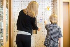 选择眼镜的母亲和儿子在商店 免版税库存照片