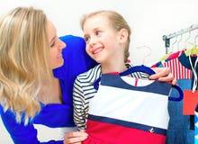选择礼服的小女孩和她的妈妈 免版税库存照片