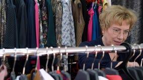 选择礼服的愉快的资深妇女,当购物在时髦的衣裳时商店  股票录像