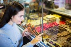 选择美好的巧克力的妇女 免版税库存图片