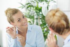 选择耳环的高兴的年轻女人 免版税库存照片