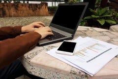选择聚焦和浅景深企业人的手的键入有黑屏、图和流动酸碱度的一台膝上型计算机 免版税库存图片