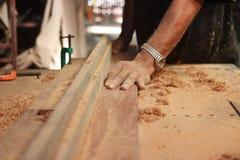 选择聚焦和浅景深 一块木头的正面图在路由器桌上被刮用木匠的人工 库存图片