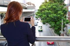 选择聚焦和浅景深 的妇女拍交通汽车的照片后面观点在有流动巧妙的电话的城市 库存图片