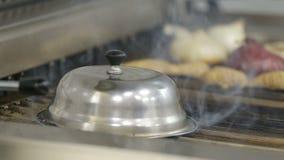 选择聚焦拿着不锈钢热的食物扣人心弦的钳子钳位的妇女手油煎在格栅的肉和菜食物 股票视频