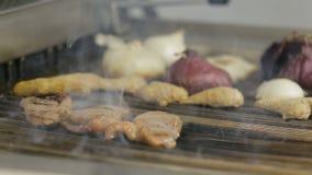 选择聚焦拿着不锈钢热的食物扣人心弦的钳子钳位的妇女手油煎在格栅的肉和菜食物 股票录像