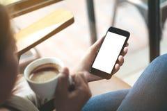 选择聚焦拿着电话的妇女手坐在咖啡嘘 免版税库存照片
