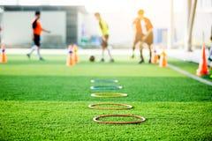 选择聚焦敲响梯子标志的和锥体是足球在绿色人为草皮的训练器材与模糊的孩子球员 免版税库存照片