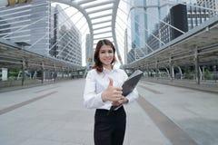 选择聚焦看起来确信和显示重击的在手边快乐的年轻亚裔女实业家签到城市背景 免版税库存图片