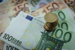 选择聚焦被堆积与欧洲钞票的欧洲硬币作为财政概念 免版税图库摄影