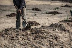 选择聚焦,农夫对工作的开掘土壤 免版税图库摄影
