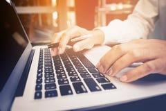 选择聚焦/年轻商人多任务使用膝上型计算机 库存图片