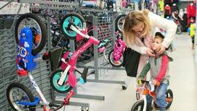 选择自行车,安全第一,五颜六色的自行车,家庭参观的玩具商店的少妇和儿子 股票视频