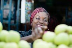 选择苹果的微笑的少妇在街市上 免版税库存照片