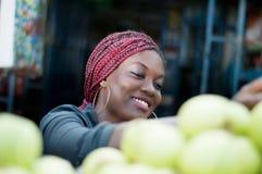 选择苹果的微笑的少妇在街市上 库存图片