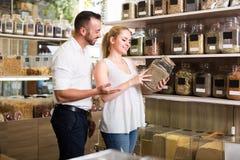 选择草本和香料的夫妇在商店 免版税图库摄影
