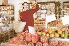 选择蕃茄的可爱的年轻女性顾客画象  库存图片