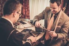 选择衣服的裁缝和客户材料 免版税库存照片
