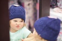 选择衣裳在商店,适合的被编织的帽子的逗人喜爱的小女孩 免版税图库摄影
