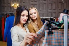 选择衣裳的两个俏丽的女孩的图象从在百货商店的新的收藏 免版税库存图片