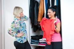 选择衣裳的两个妇女朋友 免版税库存图片