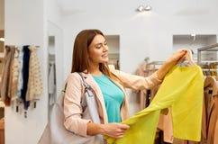 选择衣裳的愉快的妇女在服装店 免版税库存照片