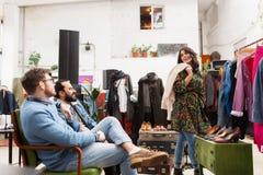 选择衣裳的朋友在葡萄酒服装店 免版税图库摄影