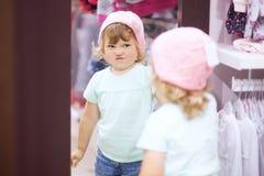 选择衣裳的逗人喜爱的小女孩在商店,适合被编织 库存图片