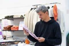 选择衬衣的便衣的人在服装店商店 库存图片