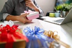 选择赠礼创造性的有礼物的手和手 礼物熟食店 库存照片