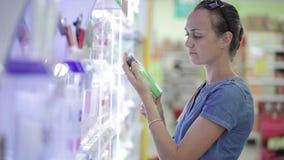 选择身体关心产品的可爱的妇女在超级市场 影视素材