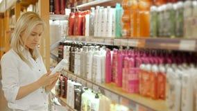 选择身体关心产品的美丽的妇女在超级市场 库存图片