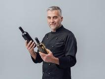 选择酒瓶的厨师 免版税库存照片