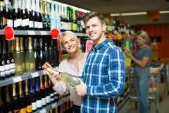 选择酒的家庭在食物店 免版税库存图片