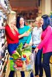 选择酒的小组美丽的女孩在超级市场 库存图片