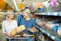 选择酥皮点心的成熟妇女在超级市场 免版税库存照片