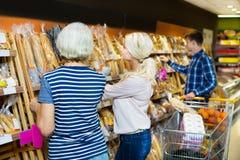 选择酥皮点心的成熟妇女在超级市场 库存照片