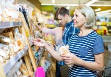选择酥皮点心的成熟妇女在超级市场 免版税图库摄影