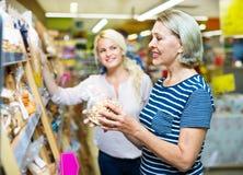选择酥皮点心的成熟妇女在超级市场 库存图片