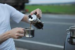 选择酿造咖啡在一辆汽车的敞篷的法国新闻中在路一边的在旅途上 免版税库存照片