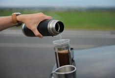 选择酿造咖啡在一辆汽车的敞篷的法国新闻中在路一边的在旅途上 免版税库存图片