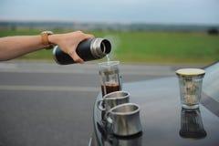 选择酿造咖啡在一辆汽车的敞篷的法国新闻中在路一边的在旅途上 免版税图库摄影