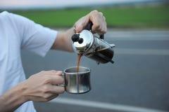选择酿造咖啡在一辆汽车的敞篷的法国新闻中在路一边的在旅途上 库存图片