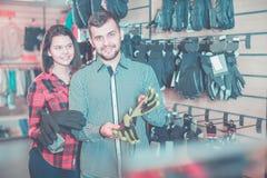 选择防护手套的年轻夫妇 库存图片