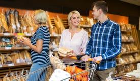 选择面包和酥皮点心的普通的顾客 免版税库存图片