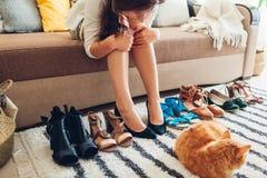 选择鞋子和试穿他们的妇女在家 做的艰难的选择由凉鞋、脚跟和舱内甲板 免版税库存照片